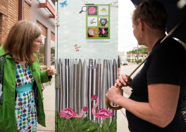 Members of the Prospect Park Association take a tour of utility boxes in the area that have been wrapped in art by local artists. The project was completed in an effort to stop graffiti and bring beauty to the neighborhood. - photo courtesy MN Daily